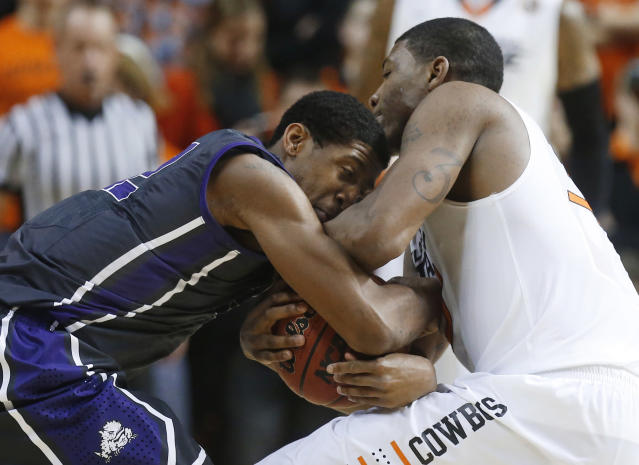 TCU guard Jarvis Ray, left, and Oklahoma State guard Marcus Smart compete for the ball during the second half of an NCAA college basketball game in Stillwater, Okla., Wednesday, Jan. 15, 2014. Oklahoma State won 82-50. (AP Photo/Sue Ogrocki)