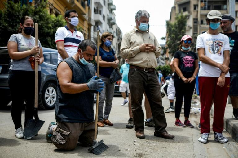 Volunteers and civil society members, mask-clad due to the COVID-19 pandemic, attend an outdoor Sunday mass held by a Maronite Christian priest in the Mar Mikhael neighbourhood of Lebanon's capital Beirut