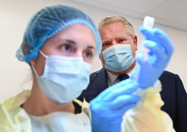 Ontario Premier Doug Ford watches a health-care worker prepare a dose of the Pfizer-BioNTech COVID-19 vaccine at a UHN vaccine clinic in Toronto on Thursday, January 7, 2021.