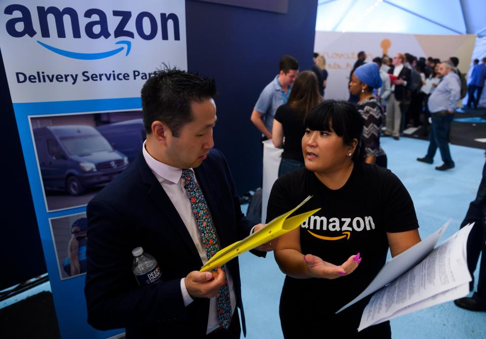 An Amazon recruiter (R) gives advice to a job seeker at an Amazon Career Day event, where recruiters help candidates build interview skills, prepare them for job interviews and give them more information on the roles within the company, at Crystal City in Arlington, Virginia on September 17, 2019. - Amazon is aiming to hire more than 30,000 people across the country by early next year. (Photo by Andrew CABALLERO-REYNOLDS / AFP)        (Photo credit should read ANDREW CABALLERO-REYNOLDS/AFP via Getty Images)