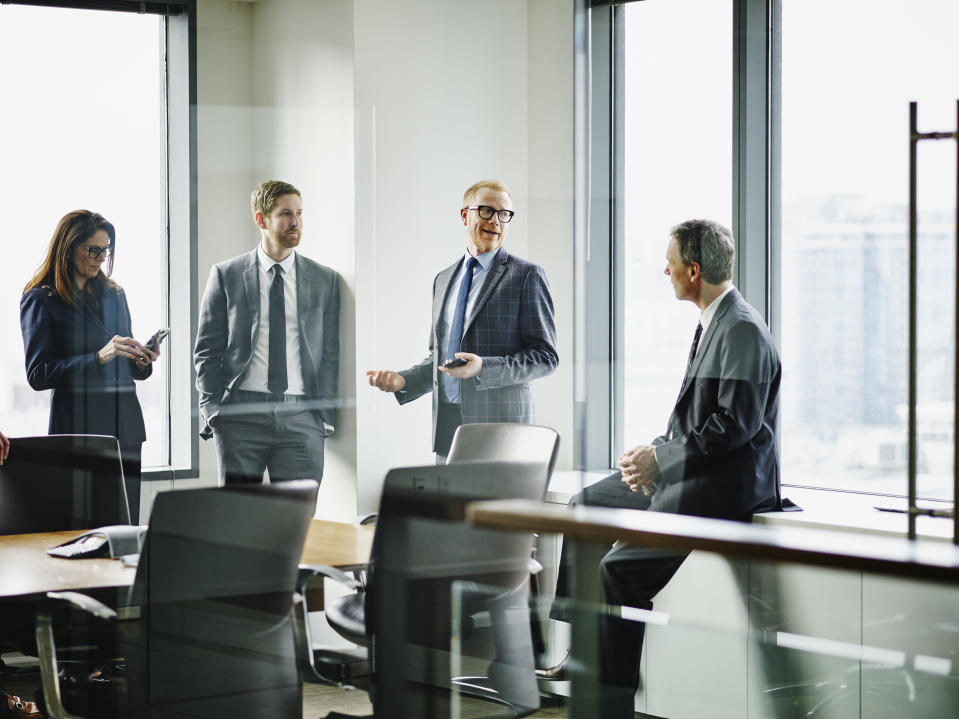 Business executives in discussion in office conference room after team meeting