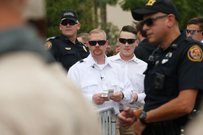 <p>Members of Richard Spencer's security team, in white, stand behind police and decide who gets tickets to a speech by white nationalist Richard Spencer, who popularized the term 'alt-right', at the University of Florida campus on Oct.19, 2017 in Gainesville, Fla. (Photo: Brian Blanco/Getty Images) </p>