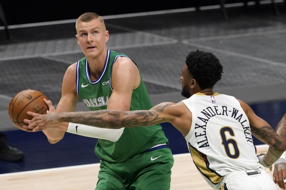 Dallas Mavericks center Kristaps Porzingis, left, works against New Orleans Pelicans guard Nickeil Alexander-Walker (6) for a shot opportunity during the first half of an NBA basketball game in Dallas, Wednesday, May 12, 2021. (AP Photo/Tony Gutierrez)