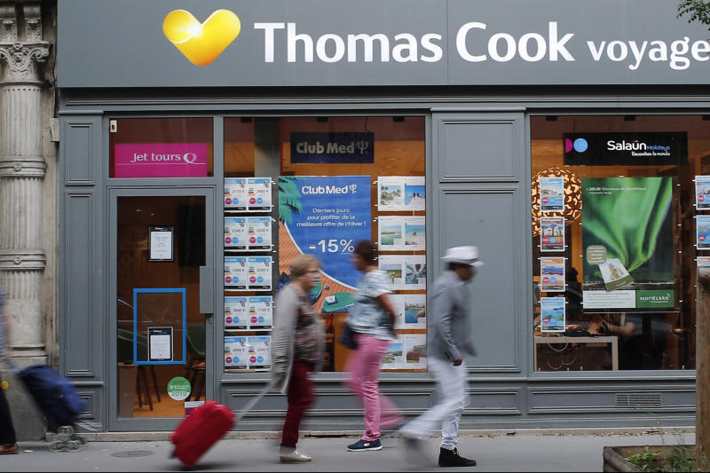 People walk past a Thomas Cook travel shop in Paris, Monday, Sept. 23, 2019. British tour company Thomas Cook collapsed early Monday after failing to secure emergency funding, leaving tens of thousands of vacationers stranded abroad. (AP Photo/Francois Mori)