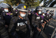Police in riot gear arrive ahead of a pro-democracy protest in front of the Parliament where Prime Minister Prayuth Chan-ocha and nine cabinet ministers are facing the fourth day of censure debate in Bangkok, Thailand, Friday, Feb. 19, 2021. They are calling for Prime Minister Prayuth Chan-ocha and his government to step down. (AP Photo/Sakchai Lalit)