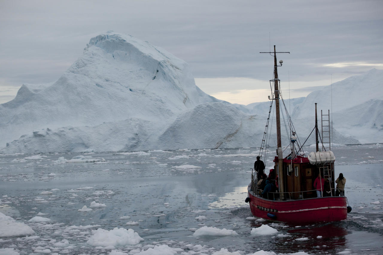 In this July 18, 2011 photo, a boat steers slowly through floating ice, and around icebergs, all shed from the Greenland ice sheet, outside Ilulissat, Greenland. (AP Photo/Brennan Linsley)