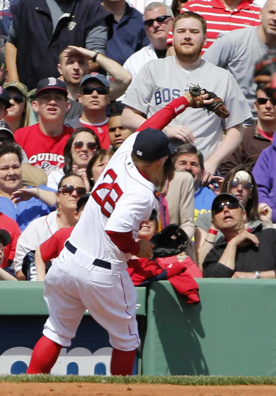 Boston Red Sox third baseman Brock Holt can't get to a foul ball off the bat of Baltimore Orioles' Nick Markakis during the third inning of a baseball game at Fenway Park in Boston Monday, April 21, 2014. (AP Photo/Winslow Townson)