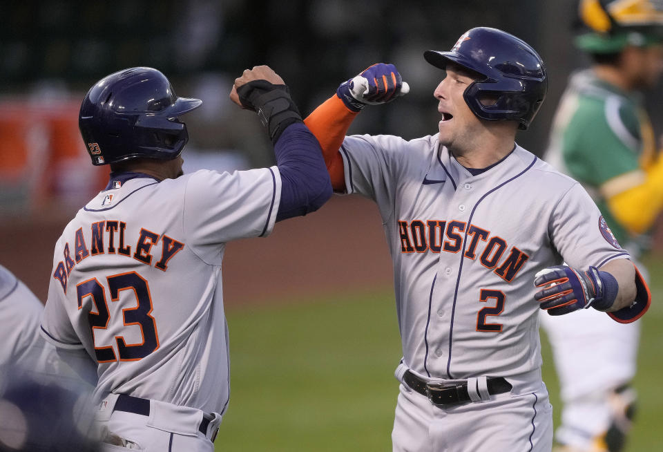 Houston Astros' Alex Bregman (2) celebrates with teammate Michael Brantley (23) after hitting a three-run home run against the Oakland Athletics during the third inning of a Friday, April 2, 2021, in Oakland, Calif. (AP Photo/Tony Avelar)