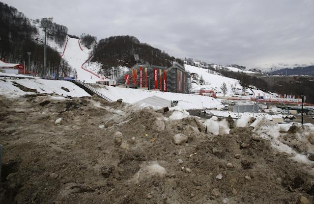 Brown, dirty snow is piled up on the road to the finish area of the alpine ski venue at the Sochi 2014 Winter Olympics, Tuesday, Feb. 11, 2014, in Krasnaya Polyana, Russia. Warm temperatures in the mountains was a factor in the cancellation of Women's downhill training on Tuesday. (AP Photo/Christophe Ena)