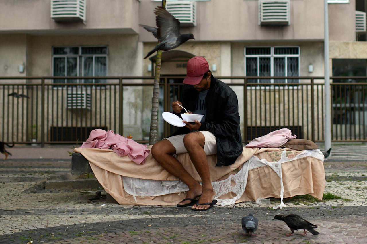 Lucas Landau / reuters - A homeless person eats after receiving food from a group of residents of the Chapeu Mangueira slum, during the coronavirus disease (COVID-19) outbreak, at Copacabana neighborhood in Rio de Janeiro, Brazil, April 11, 2020.  REUTERS/Lucas Landau     TPX IMAGES OF THE DAY