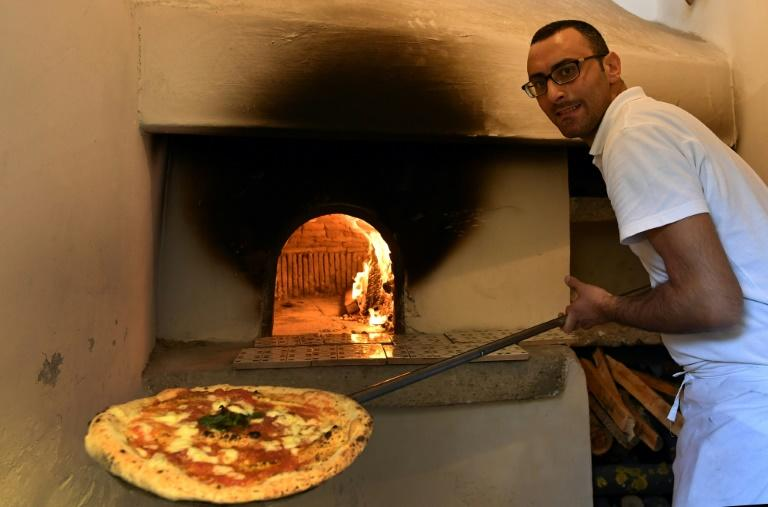 A pizza maker uses the stone oven where the first pizza Margherita was cooked