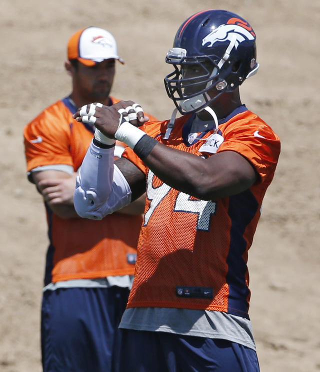 Denver Broncos defensive end DeMarcus Ware signs a defensive play during drills at minicamp at the NFL football teams training facility in Englewood, Colo., on Thursday, June 12, 2014. (AP Photo/Ed Andrieski)