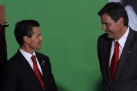 Mexico's President Enrique Pena Nieto, left, speaks with Brian Smith, president of Coca Cola Company Latin America, during the unveiling of Mexico's strategy to combat diabetes and obesity in Mexico City, Thursday, Oct. 31, 2013. (AP Photo/Marco Ugarte)