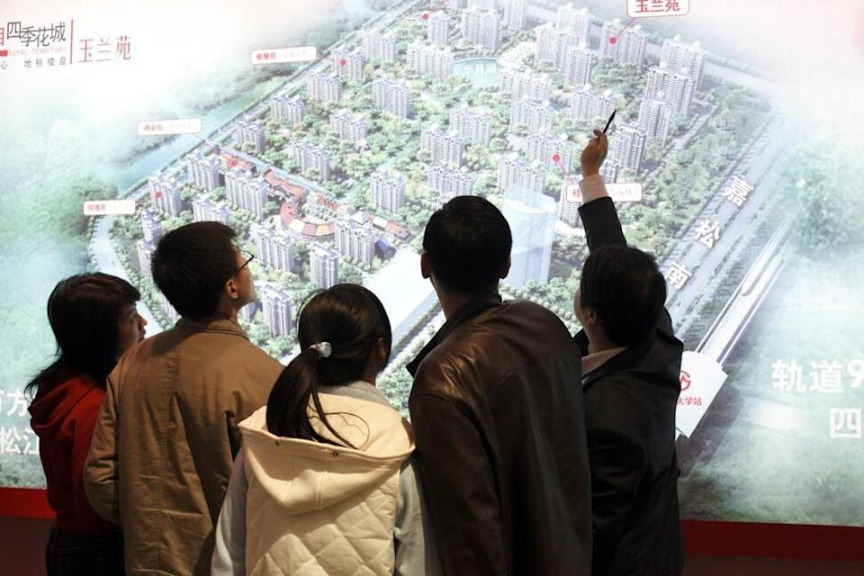 An agent shows potential buyers the layout of a new residential development at a real estate fair in Shanghai on 15 March, 2009. Photo: Corbis via Getty Images