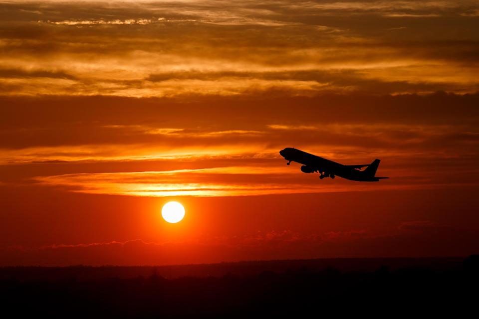 Airplane taking off in sunset sky