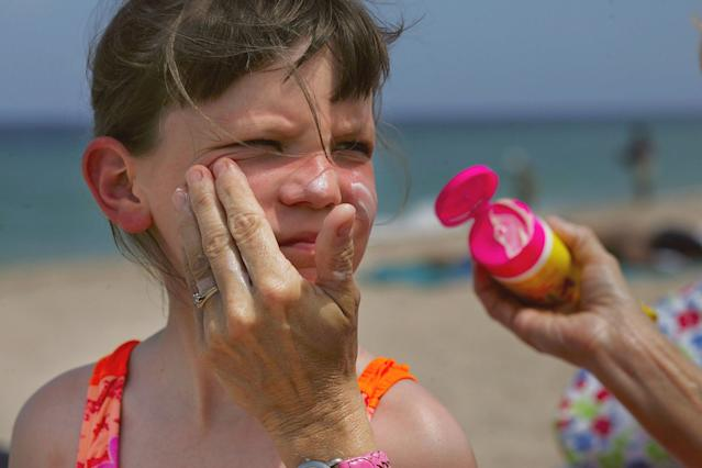 Sharon Doyle puts sunscreen on the face of 9-year-old Savannah Stidham as they visit the beach in Fort Lauderdale, Fla. (Photo by Joe Raedle/Getty Images)