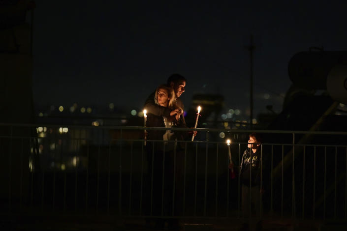 "A family holding candles gather on a rooftop of a building during a lockdown order by the government to prevent the spread of the coronavirus in Athens, on Sunday, April 19, 2020. Greeks celebrated the Resurrection of Christ very differently Saturday night: confined at home, instead of massively congregating in churches. And they had to do without the ""Holy Light"" from Jerusalem, which arrived in Athens but was not distributed, as authorities remained ready to crack down on anyone who violated the strict curfew imposed almost a month ago. (AP Photo/Michael Varaklas)"