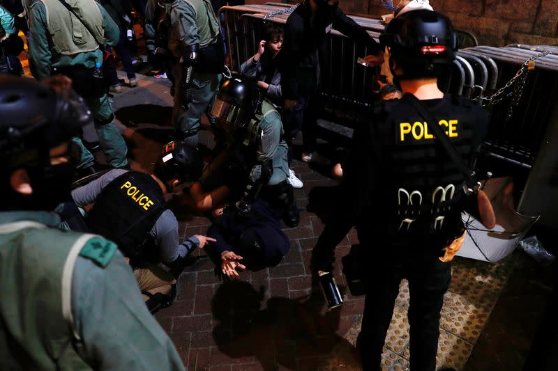 Riot police officers detain an anti-government protester during a demonstration on New Year's Eve outside Mong Kok police station in Hong Kong