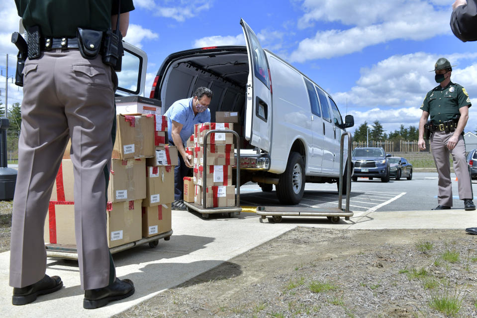 FILE - In this May 11, 2021 file photo, a clerk with the New Hampshire Department of State unloads boxes of ballots, in Pembroke, N.H., for a forensic audit of a New Hampshire legislative election. Auditors concluded in a report released Tuesday, July 13, 2021, that miscounts in a New Hampshire election were caused by the way ballots were folded. (AP Photo/Josh Reynolds, File)