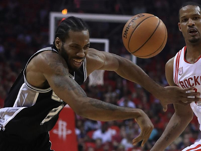 Kawhi Leonard of the San Antonio Spurs battles for the ball against Trevor Ariza of the Houston Rockets during Game Three of the NBA Western Conference Semi Finals at Toyota Center
