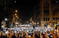 Demonstrators hold up their phones during a protest after a verdict in a trial over a banned independence referendum, in Barcelona