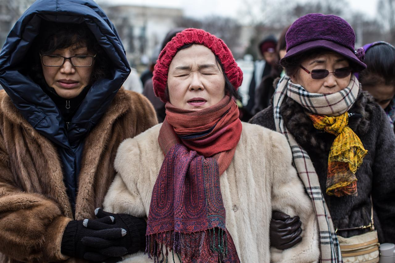 Anti-abortion protestors Grace Jang, Sharon Lee, and Virginia Kim, anti-abortion rotesters from Springfield, Virginia, pray before the March for Life on January 25, 2013 in Washington, DC. The pro-life gathering is held each year around the anniversary of the Roe v. Wade Supreme Court decision. (Photo by Brendan Hoffman/Getty Images)