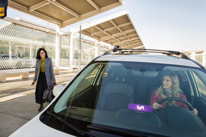 A woman in the driver's seat of a parked car with the Lyft logo on the dashboard while another woman approaches the car.