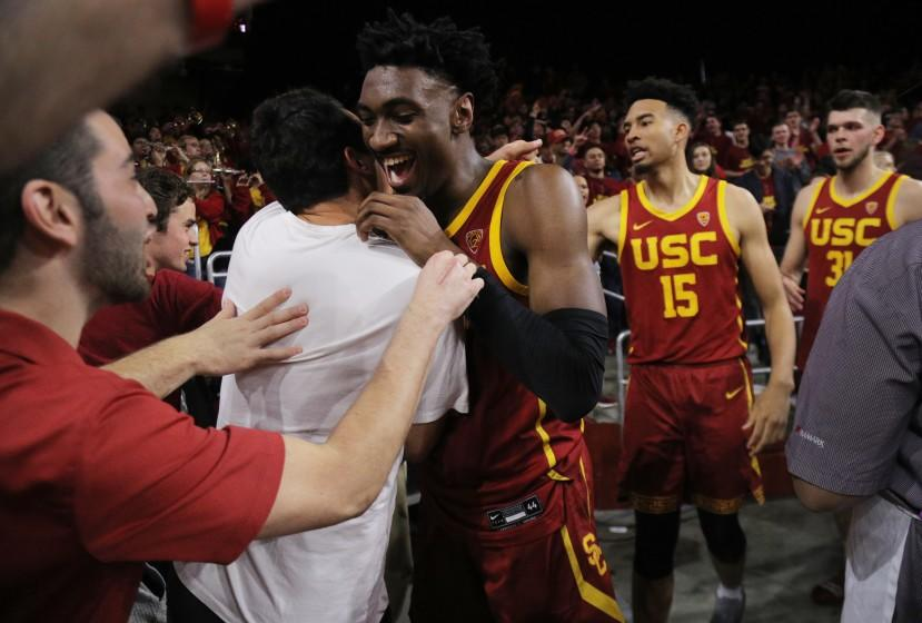 USC's Jonah Mathews, middle, celebrates with fans after making a game-winning three-pointer to beat UCLA on March 7, 2020.