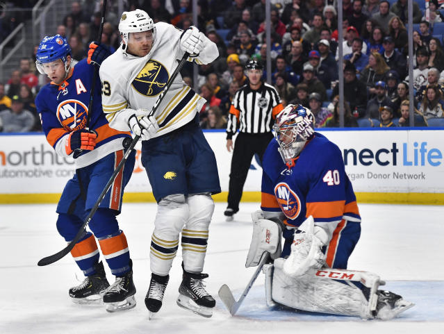 Buffalo Sabres center Sam Reinhart, center, is hit in the back by a shot as New York Islanders right wing Josh Bailey, left, and goalie Semyon Varlamov (40) look on during the second period of an NHL hockey game in Buffalo, N.Y., Saturday, Nov. 2, 2019. (AP Photo/Adrian Kraus)