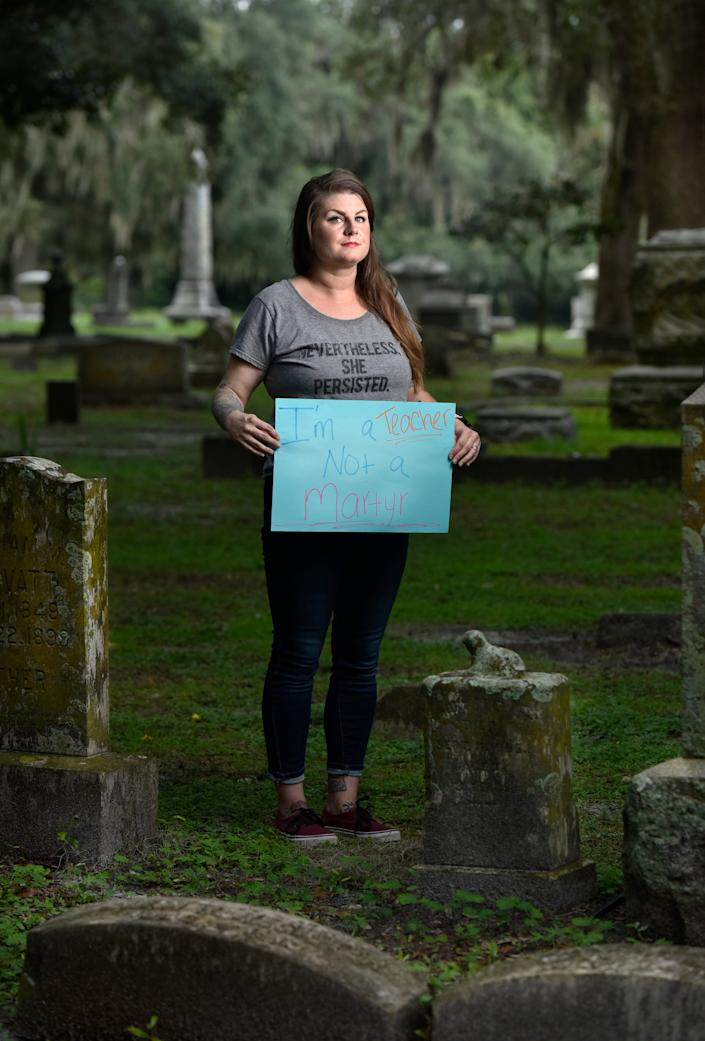 """Whitney Reddick, a special education teacher in Jacksonville, Fla., holds a sign that says """"I'm a teacher, not a martyr"""" after participating in a march protesting the opening of schools during the pandemic that ended at a cemetery."""