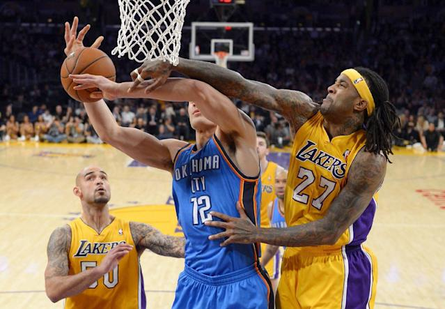 Los Angeles Lakers forward Jordan Hill, right, blocks a shot by Oklahoma City Thunder center Steven Adams, center, of New Zealand, as center Robert Sacre stands near during the first half of an NBA basketball game Thursday, Feb. 13, 2014, in Los Angeles. (AP Photo/Mark J. Terrill)