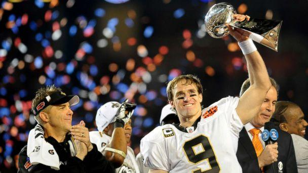 PHOTO: Drew Brees of the New Orleans Saints holds up the Vince Lombardi Trophy on the podium as head coach Sean Payton looks on after defeating the Indianapolis Colts in Super Bowl XLIV, Feb. 7, 2010, at Sun Life Stadium in Miami Gardens, Florida. (Rob Tringali/Sportschrome/Getty Images)