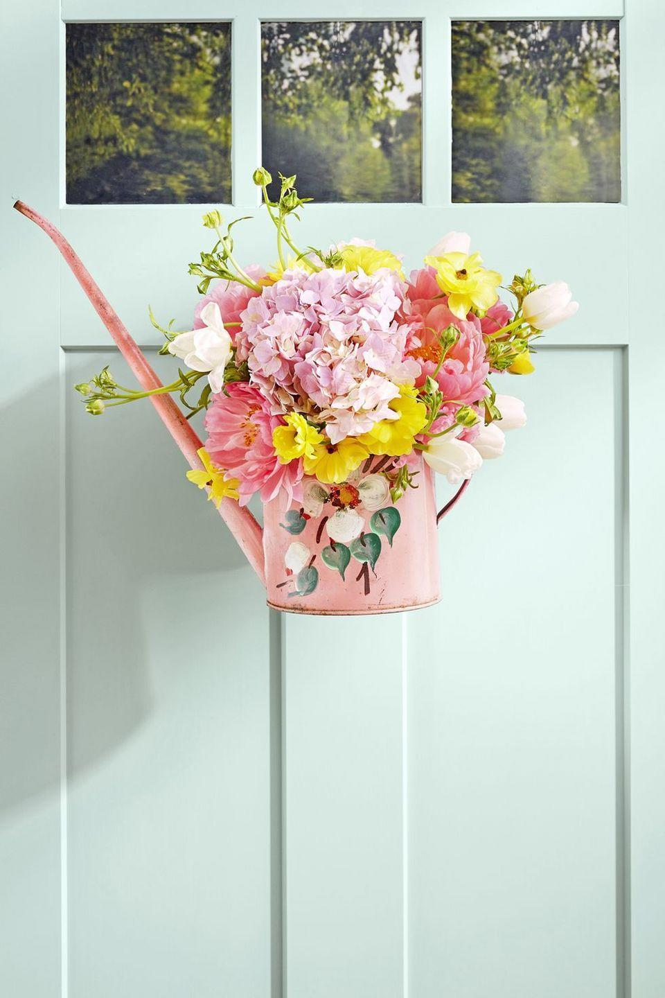 """<p>Loop wire around the handle of your favorite watering can, hang it from your door, then fill with fresh blooms. It's as easy as that!</p><p><a class=""""link rapid-noclick-resp"""" href=""""https://www.amazon.com/Calunce-Tradition-Watering-LitreWatering-Flowers/dp/B07DC4XWCK?tag=syn-yahoo-20&ascsubtag=%5Bartid%7C10050.g.4088%5Bsrc%7Cyahoo-us"""" rel=""""nofollow noopener"""" target=""""_blank"""" data-ylk=""""slk:SHOP PINK WATERING CANS"""">SHOP PINK WATERING CANS</a></p>"""