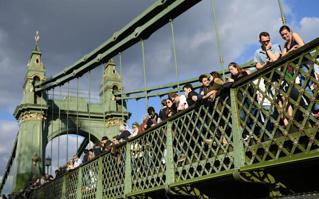 <span>Spectators gather on Hammersmith Bridge</span> <span>Credit: GETTY IMAGES </span>
