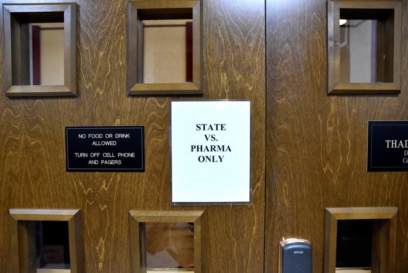 A sign is seen on the outside of the courtroom on the first day of a trial of Johnson & Johnson in Norman