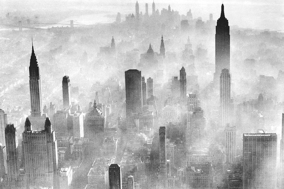<p>The physical effects of industrialization are seen as smog partially obscures the city skyline. </p>