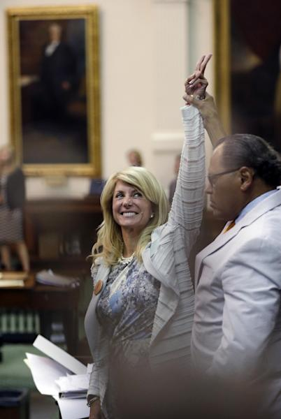 Sen. Wendy Davis, D-Fort Worth, left, who tries to filibuster an abortion bill, reacts as time expires, Tuesday, June 25, 2013, in Austin, Texas. Amid the deafening roar of abortion rights supporters, Texas Republicans huddled around the Senate podium to pass new abortion restrictions, but whether the vote was cast before or after midnight is in dispute. If signed into law, the measures would close almost every abortion clinic in Texas. (AP Photo/Eric Gay)
