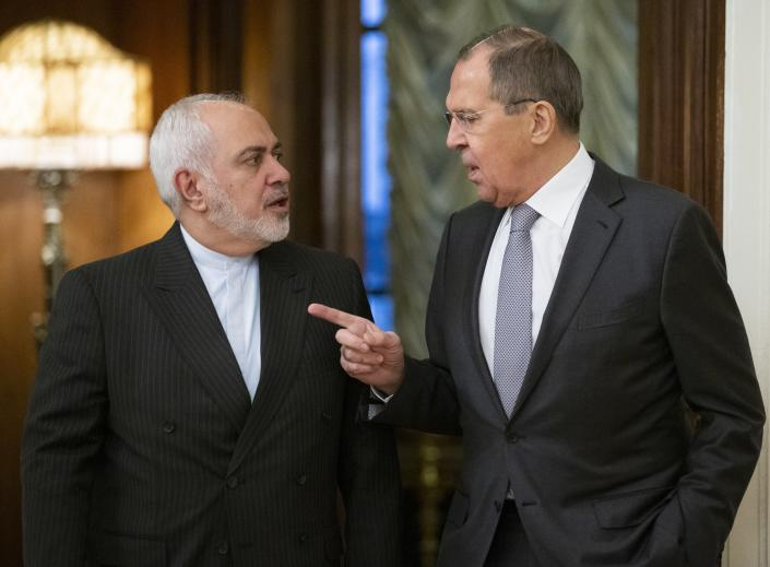 Russian Foreign Minister Sergey Lavrov, right, gestures as he and Iranian Foreign Minister Mohammad Javad Zarif while entering a hall for the talks in Moscow, Russia, Monday, Dec. 30, 2019. (AP Photo/Alexander Zemlianichenko)