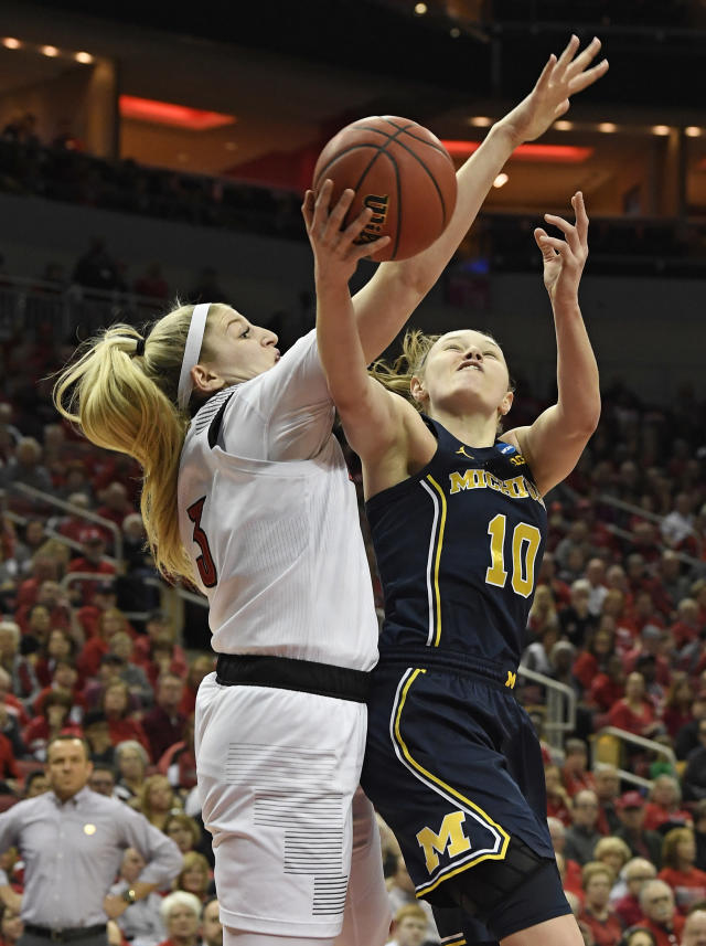 Michigan guard Nicole Munger (10) is fouled by Louisville forward Sam Fuehring (3) while attempting to shoot during the first half of a second-round game in the NCAA women's college basketball tournament in Louisville, Ky., Sunday, March 24, 2019. (AP Photo/Timothy D. Easley)