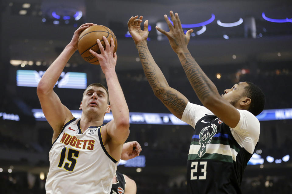Denver Nuggets' Nikola Jokic (15) grabs a rebound next to Milwaukee Bucks' Sterling Brown during the first half of an NBA basketball game Friday, Jan. 31, 2020, in Milwaukee. (AP Photo/Aaron Gash)