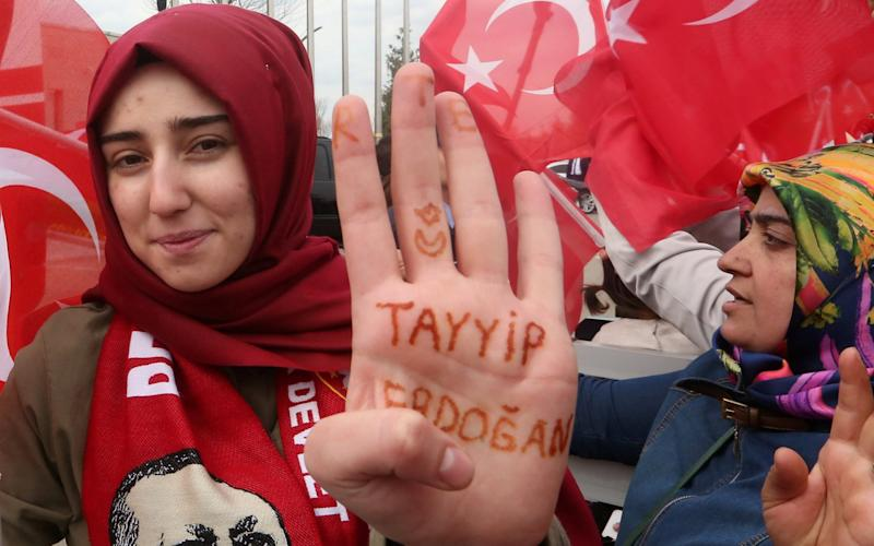 "A woman shows her hand, which reads ""Tayyip Erdogan"", as she waits for the arrival of Turkish President Tayyip Erdogan at Esenboga Airport in Ankara - Credit:  REUTERS/Stringer"