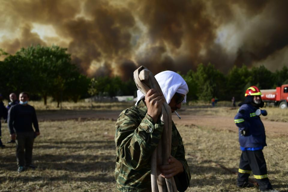 A man holds a water hose during a wildfire in Kryoneri area, northern Athens, Greece, Thursday, Aug. 5, 2021. Wildfires rekindled outside Athens and forced more evacuations around southern Greece Thursday as weather conditions worsened and firefighters in a round-the-clock battle stopped the flames just outside the birthplace of the ancient Olympics. (AP Photo/Michael Varaklas)