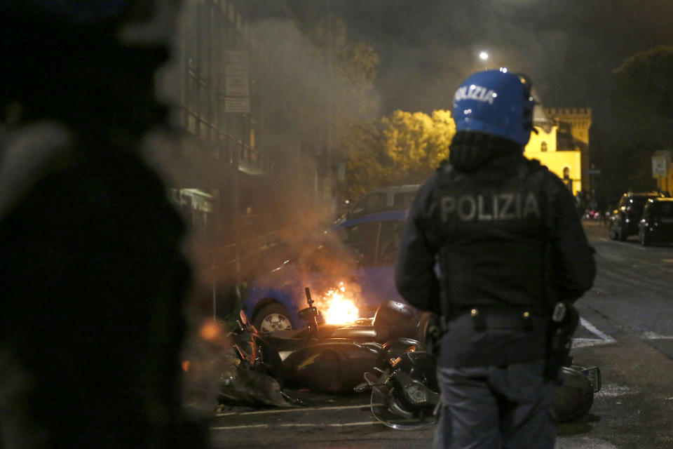 A police officer patrols as a bike burns during a protest called by Forza Nuova far right group against the government restriction measures to curb the spread of COVID-19, in Rome Saturday, Oct. 24, 2020. A midnight-to-5 a.m. curfew in Italy's Lazio region, which includes Rome, begins on Friday and lasts for 30 days, under orders from regional governor Nicola Zingaretti. (Cecilia Fabiano/LaPresse via AP)