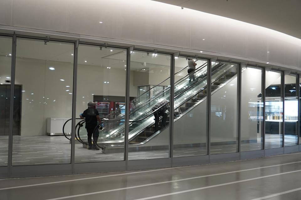 Crews were polishing the escalators moments before the doors opened to the public on Saturday morning.