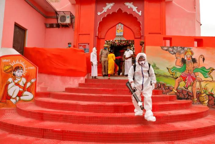 A municipal worker wearing protective gear sprays disinfectant at Hanuman Garhi temple before the arrival of India's Prime Minister Narendra Modi ahead of the foundation laying ceremony for a Hindu temple in Ayodhya