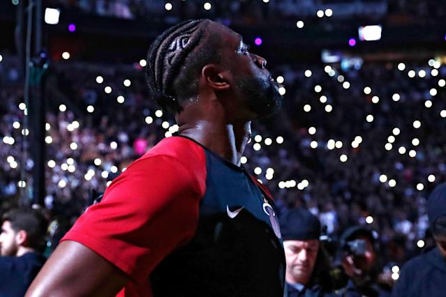 Miami Heat guard Dwyane Wade stands on the court during a ceremony honoring Wade, who is playing his final home regular season game when the Heat host the Philadelphia 76ers, Tuesday, April 9, 2019, in Miami. Wade is retiring at the end of the season. (AP Photo/Brynn Anderson)