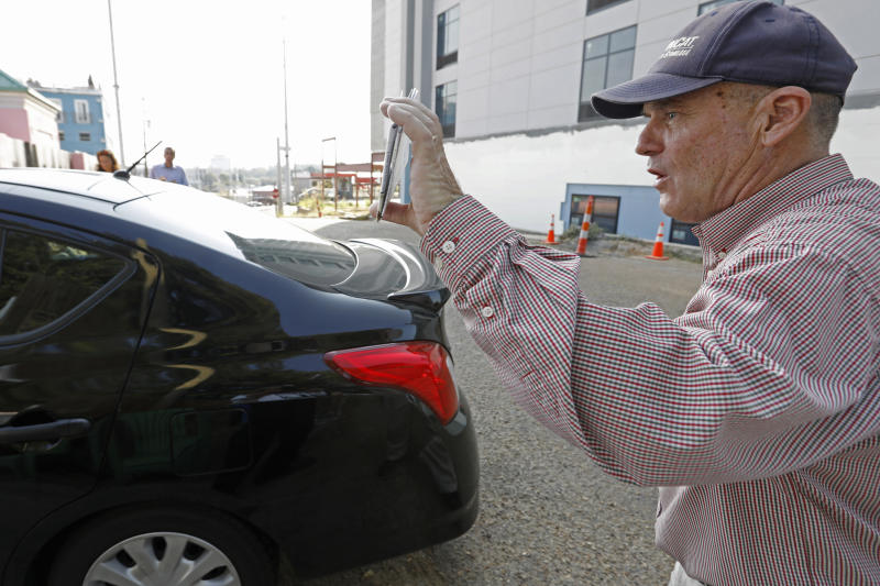 Anti abortion activist Doug Lane, calls out to a woman driving into the Jackson Women's Health Organization clinic in Jackson, Miss., Wednesday, Oct. 2, 2019. The Jackson City Council voted 3-1 Tuesday to enact a local law limiting amplified sound outside health care facilities and creating buffer zones to move protesters further from the entrances. The law is set to take effect in about a month, and opponents say it unconstitutionally limits their right to free speech. A court challenge is likely. (AP Photo/Rogelio V. Solis)