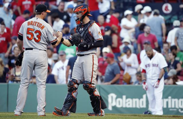 Boston Red Sox's Jonny Gomes, background right, looks down as Baltimore Orioles' Zach Britton (53) and Caleb Joseph celebrate after defeating the Red Sox 7-6 in the twelfth inning of a baseball game in Boston, Sunday, July 6, 2014. (AP Photo/Michael Dwyer)