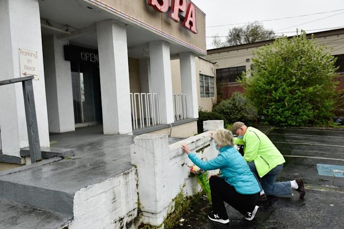 """<div class=""""inline-image__caption""""><p>John and Barbara Hayes, of Sandy Springs, Georgia, bring flowers and offer prayers at the steps of Gold Spa.</p></div> <div class=""""inline-image__credit"""">Virginie Kippelen/AFP via Getty</div>"""