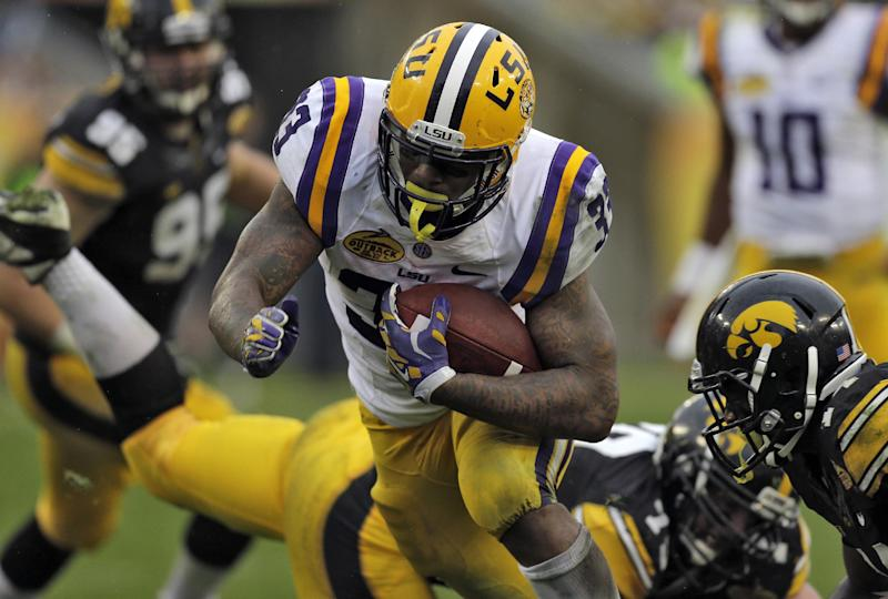 LSU running back Jeremy Hill (33) rushes through the Iowa defense, including defensive back Desmond King, right, to score on a 14-yard touchdown run during the second quarter of the Outback Bowl NCAA college football game Wednesday, Jan. 1, 2014, in Tampa, Fla. (AP Photo/Chris O'Meara)